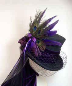 Black top hat trimmed in purple velvet, taffeta, lace and satin. Side feathers in purple speckled feather and peacock feathers. Merry Widow face veil, rear mid back veil in fine black tulle, purple ribbon and taffeta ruffles. Made in my own workshop in Scotland https://www.etsy.com/uk/shop/Blackpin?ref=hdr_shop_menu