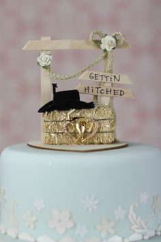 "This adorable ""Getting Hitched"" Western Wedding Cake Topper features a wooden hitching post with a miniature hay bale and a pair of gold double hearts encrusted with crystals."