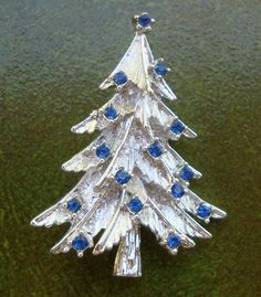 Vintage silver tone metal Christmas tree brooch, with faceted blue prong set rhinestones, mid century