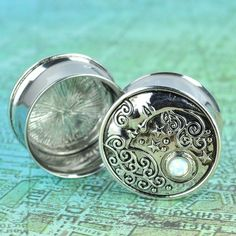 Steel plugs with crescent moon and opal Quantity: Sold as 1 pair (2 pieces) Tunnel material: 316L stainless steel Face design material: zinc alloy Opal: synthetic opal Style: round tunnel with a face