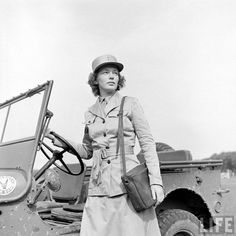 A WAC standing next to her jeep, she's wearing the summer uniform with the matching visor hat and has her gloves between her belt. The purse she has with her, I don't recognize ~