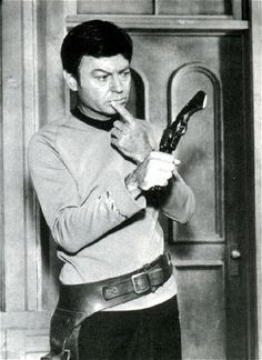 A gag publicity photo from 'Spectre of the Gun' featuring De Kelley (who did dozens of westerns prior to Trek) confused by the antique firearm.