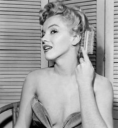 Marilyn Monroe touches up her hair.