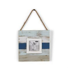 Distressed and planked beach blues wood frame hangs with jute rope. Holds 3' x 3' photo inserted through back of frame.