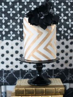 Gold and white chevron-patterned cake with a pop of black