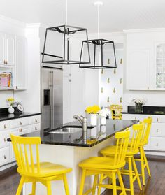 This eclectic kitchen features bright yellow bar stools, a fun pop of colour against dark hardwood floors, clean white cabinets, and balck granite countertops. Interesting lighting adds a modern spin to the space.