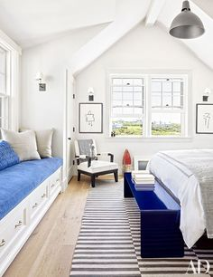 A child's room is furnished with a pendant light and blue and white textiles.
