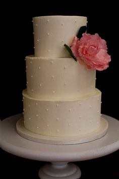 Buttercream with dotted swiss design.  Decorated with a sugar peony and leaves.  Serves 65-75
