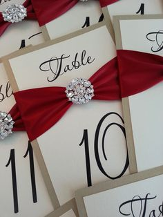 Champagne gold & red satin ribbon table numbers decorated with an elegant Crystal embellishment. Perfect for Fall/winter weddings!