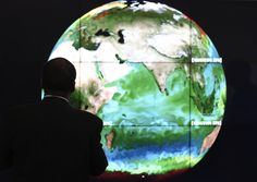 A conference attendee looks at a projection of Earth on the opening day of the COP 21 United Nations conference on climate change, in November on the outskirts of Paris.