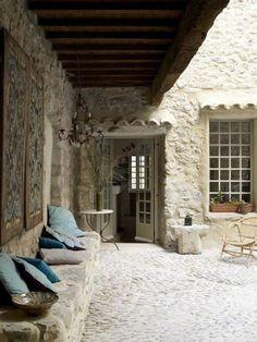 banc de pierre & ciment ; sol en galets ; tuiles au-dessus de portes & fenêtres