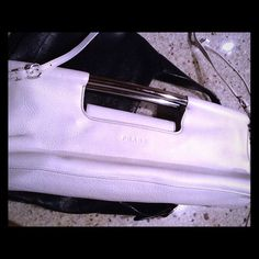 White leather Prada hand bag.   Price drop!!! This was a gift from a client.   Never use it and trying to buy a Louis Vuitton artsy.  .it has shoulder straps or can be used as a clutch.  Authentic Prada. Silver handles.  Beautiful bag. Ill upload more photos upon request.. Prada Bags