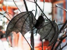 Bats in the Branches  Add some overhead interest to your dinner table with bats suspended from bare branches. All you'll need are rubber bats from the craft store and clear fishing line. Before attaching the bats, make sure the selected branch is strong enough to support the weight.