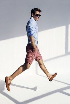 Shop this look on Lookastic:  http://lookastic.com/men/looks/light-blue-dress-shirt-pink-shorts-brown-loafers-navy-sunglasses/11341  — Navy Sunglasses  — Light Blue Dress Shirt  — Brown Suede Loafers  — Pink Shorts