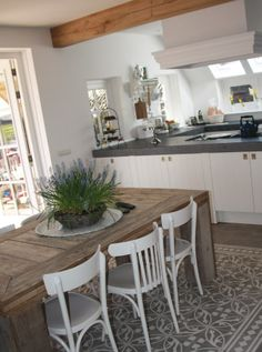Vloer voor in de keuken. Eetkamertafel oud hout met witte keukenstoelen. Mooie witte landelijke simpele keuken.