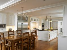 Traditional kitchen, white cabinetry, oak floors, industrial lighting and rustic table.  Huestis Tucker Architects.