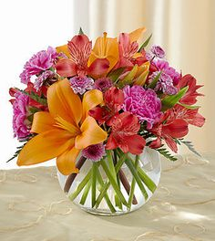 Birthday Flowers - Light of My Life Bouquet by FTD - The Light of My Life Bouquet by FTD offers your special recipient fresh vibrant color to brighten their day! Orange Asiatic Lilies, fuchsia carnations, red Peruvian Lilies, lavender chrysanthemums and lush greens are perfectly arranged in a clear glass bubble bowl vase to send your sweetest sentiments across the miles.