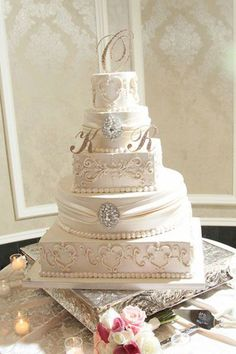 Crystal brooches and a split monogram accentuate the intricate piping on this glam cake.Cake by Palermo's Bakery