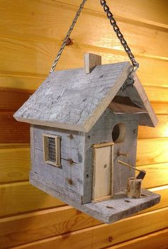 This Rustic Birdhouse shows the charm of Old world cabin living, features Reclaimed barn wood. On the front porch is a Door, and handmade miniatures ax on chopping log , One side of house has a trellis the other has a realistic window and screen. This Birdhouse would look Nice either