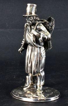 Paliteiro de prata francesa representando figura masculina de cartola com cestos nas costas. Contras