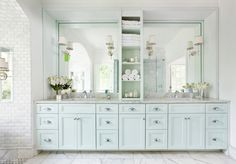 Beautiful bathroom vanity - love the soft blue vanity, silver pulls, carrera marbletop, large mirrors, and sconce lights