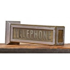 """largely intact c. 1930's art deco style illuminated double-sided building lobby """"telephone"""" wall-mount sign - fabricator unknown  UR #: UR-10773-11  DESCRIPTION    very unique c. 1930's american art deco machine age interior commercial building lobby illuminated """"telephone"""" sign. comprised largely of brass with nickel-plated finish. the two plate glass sign panels containing the word """"telephone"""" are lightly embossed"""