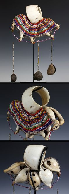 "Papua New Guinea ~ Vakuta Island, Maline Bay Province | Massim ""Mwali""; Kula trade object. Traditionally worn as an arm ornament. The large central conus shell ring, with 5 large egg-shell cowrie shell attachments. Beautifully adorned with, jobs tears and other seeds; glass and metal beads and three large suspended seed attachments. 
