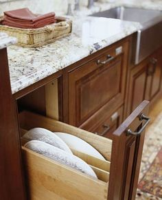 Drawers and Pullouts  Standing Tall  Disguised to look like the other cabinets, this extra-deep pullout drawer vertically organizes serving platters and shallow baking pans. Wooden dividers make the trays easy to identify and reach.  Here's a tip: Don't let other thin or shallow spaces in the kitchen go to waste. They're ideal for storing bakeware and platters.
