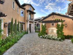 Tuscan roof tiles, climbing greenery and Old World-inspired fountains and fixtures make this Italian-style courtyard a charming and enchanting walk-through.