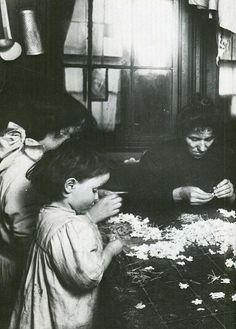 Family making artificial flowers in their house in  1910.The youngest is 3 years old.