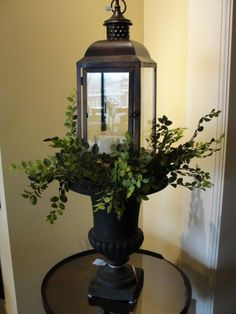 lantern atop an urn with greenery...o i have one like this and i will make it look good !!!