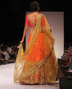Orange Lehenga with Gold Embroidery paired with red long sleeves blouse and yellow net dupatta.