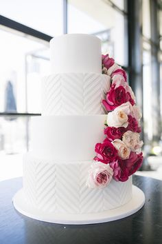 White cake with chevron pattern and pink flowers