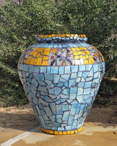 The Chief is a glass vase that is covered with hand cut Mexican talavera tile in a beautiful turquoise and golden yellow motif. MutterWorks