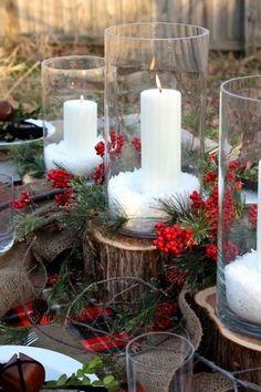 Pour plus de simplicité, utilisez des bûches comme support à votre décoration. Placez-y des bougies enfermées dans des vases enneigés et entourées les de baies de houx et de branches de sapin.