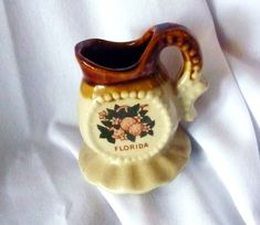 Vintage Florida souvenir pitcher with orange blossoms, citrus fruit, and foliage