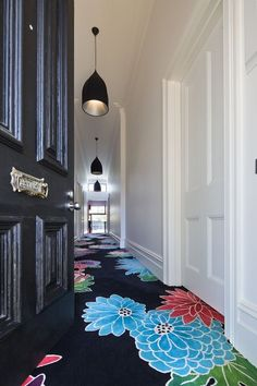 Black floral rug down hallway, white walls, black pendants, black painted door.