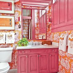 Magenta-and-orange toile wallpaper envelops the room and matches the pink cabinetry, trim, and shutters.