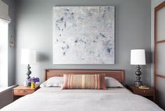 Gray bedroom with striped pillow, speckled artwork, and matching table lamps on bedside tables
