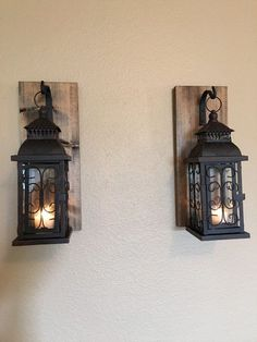 THIS IS A BEAUTIFUL SET OF TWO WALL SCONCES WITH BROWN AND BLACK METAL LANTERNS HANGING FROM WROUGHT IRON HOOKS. THE WOOD HAS BEEN STAINED A ESPRESSO COLOR AND ARE APPROX. 14 1/2 X 5 1/2 IN SIZE. THE LANTERNS ARE 11 1/2 X 4 1/4 INCHES. THERE IS A LARGE HINGED DOOR ON EACH LANTERN FOR EASY ACCESS TO ADD YOUR FAVORITE CANDLE. COMES WITH A LARGE SAW TOOTH HANGER ON THE BACK FOR EASY AND STURDY HANGING. ***THESE ARE TO BE USED AS DECORATION. PLEASE KEEP OUT OF REACH OF CHILDRE...