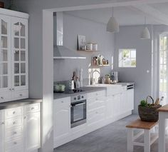 Façades blanches moulurées et murs gris perle... On se laisse séduire par cette cuisine aux airs d''autrefois.