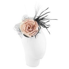 Tocado con una rosa y plumas. Cabeza maniquí fondo blanco.