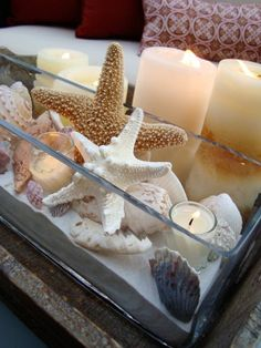 "Longing for that summertime feel during the winter months? Bring the beach right to your table. This sea-inspired centerpiece is easy to make and can be used all year round. ""A rustic wooden tray provides the base for the rectangular glass vase filled with sand, candles and a variety of seashells,"" Katrina Giles of Seaside Interiors says. Add vibrant shells and starfish for an extra boost of summer hues."