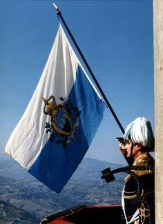The Flag of San Marino. The state and war flag of San Marino is formed by two equal horizontal bands of white (top) and light blue with the national coat of arms superimposed in the center; the coat of arms has a shield (featuring three towers on three peaks) with a closed crown on top, flanked by an oak and laurel wreath, with a scroll below bearing the word LIBERTAS (Liberty). The two colors of the flag represent peace (white) and liberty (azure).