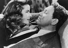 Katharine Hepburn and Spencer Tracy looking into each other eyes in a scene from the film ' Woman Of The Year', 1942. Description from gettyimages.com. I searched for this on bing.com/images