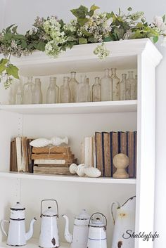 Collections of white enamelware, books and old bottles on this book shelf.