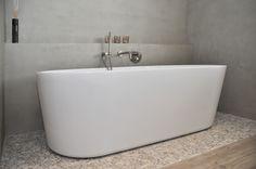 Sober en stoer betonstuc van Herijgers Badkamers - www.herijgers.nl Sfeervolle badruimte met kiezel vloer, hout-look tegels en vrijstaand bad