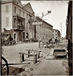 1865. Charleston, South Carolina. Archibald McLeish's Vulcan Iron Works on Cumberland Street. Left half of glass-plate stereograph, from photographs of the Federal Navy and seaborne expeditions against the Atlantic Coast of the Confederacy, 1863-1865. Note the unusually elaborate sign, as well as what seem to be the giant wheels of an artillery carriage. |