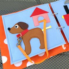 This busy / quiet book page made of felt uses a snap-hook to attach the dogs…