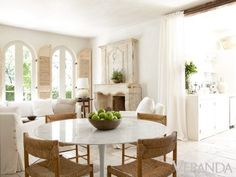TEXTURES! Saarinen tulip marble top table mixed with the roughness of the chairs, limestone fireplace, antique shutters and the linen of the slipcovered sofa - LOVE! Pamela Pierce via Veranda